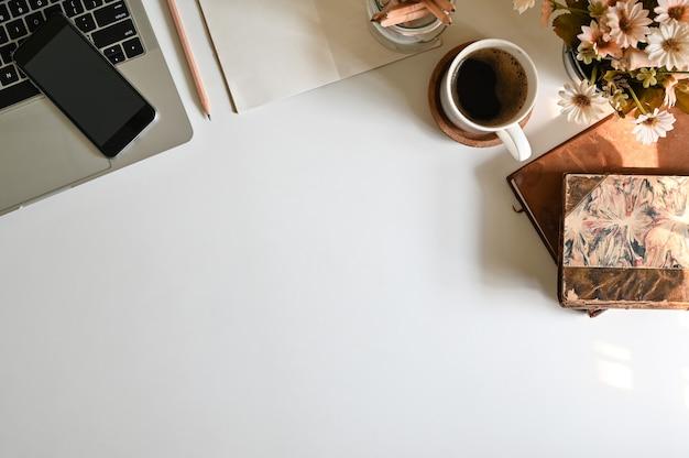 A mesa de escritório da vista superior com computador, telefone celular do café e material de escritório na tabela e nas janelas de manhã ilumina-se.