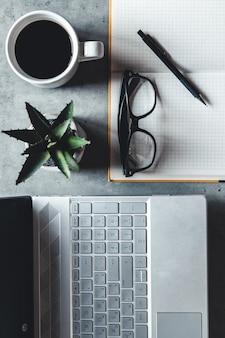 A mesa de escritório plana lay view com laptop, mouse, árvore, clipe de papel, xícara de café, caderno, lápis, óculos pretos sobre fundo branco.