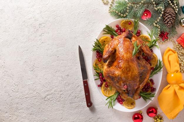 A mesa de natal com frango assado é decorada festivamente com velas.