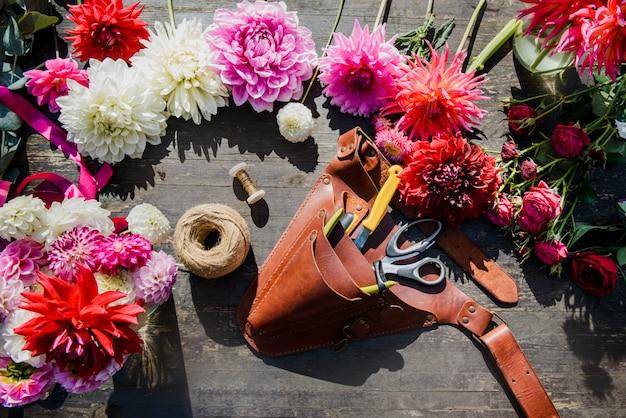A mesa de trabalho do florista com as ferramentas no fundo escuro de madeira. vista plana, vista superior