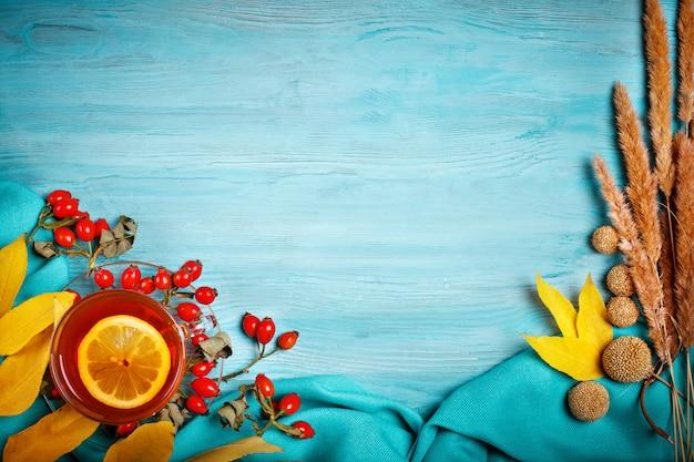 A mesa, decorada com folhas de outono, frutas e chá fresco. outono. fundo de outono.