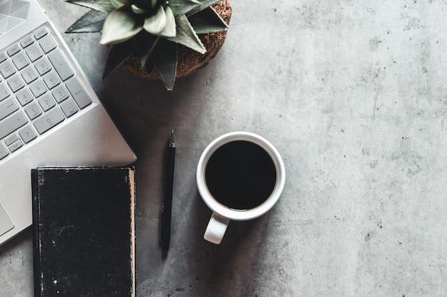 A mesa do escritório com vista plana com mouse para laptop árvore clipe de papel xícara de café caderno lápis