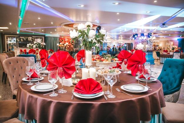 A mesa do restaurante é decorada para o evento com guardanapos vermelhos.