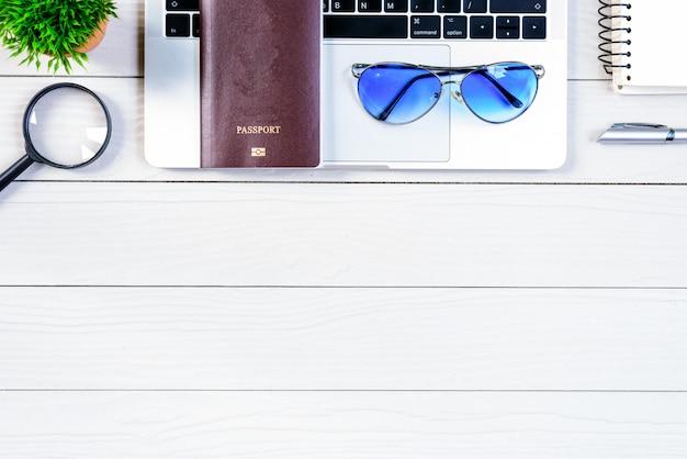A mesa do trabalhador e do empregado tem a viagem que sonha e que prepara-se para viajar e viajar em todo o mundo com o portátil e o passaporte na tabela de madeira branca da vista superior lisa da configuração.