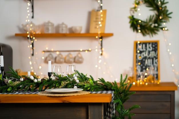 A mesa festiva de natal é decorada com galhos de uma árvore de natal, velas e guirlandas