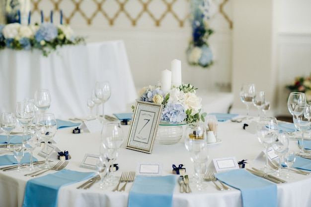A mesa festiva é decorada em cores claras com guardanapos azuis e flores sem comida