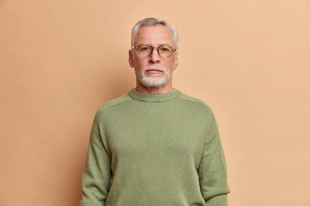 A metade do comprimento de um homem barbudo sério parece impassível na frente com uma expressão estrita, usa óculos e o macacão tem cabelos grisalhos, confiante em algo isolado sobre a parede bege do estúdio
