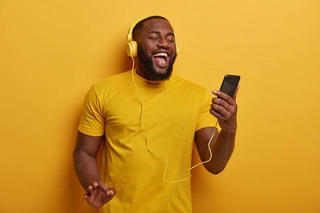 A metade do comprimento do cara negro ouve música para relaxar, segura um smartphone moderno e usa fones de ouvido, gosta de uma boa faixa, posa contra um fundo amarelo.