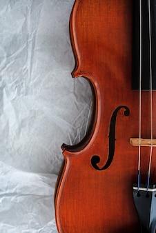 A metade do lado da frente do violino, a luz embaçada ao redor