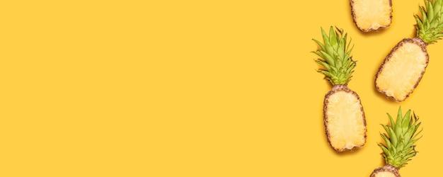 A metade fresca cortou abacaxis no fundo amarelo para o estilo mínimo.