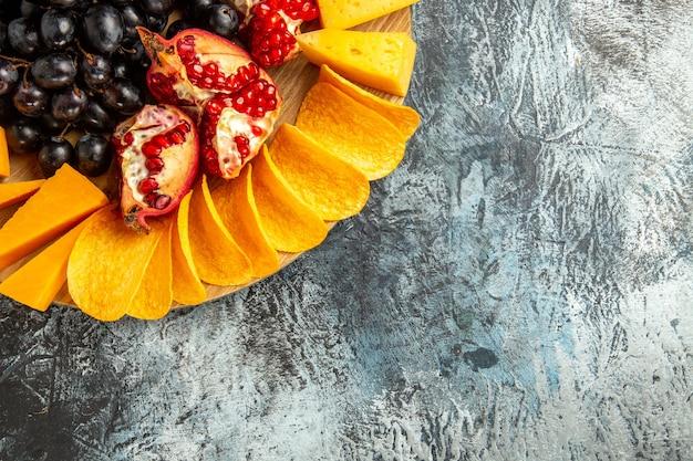 A metade superior da vista de queijo corta uvas e romã em uma placa de madeira oval em fundo escuro