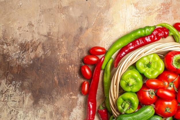 A metade superior da vista em círculo dá forma a pimentas e tomates cereja, uma cesta de legumes em um círculo sobre fundo âmbar