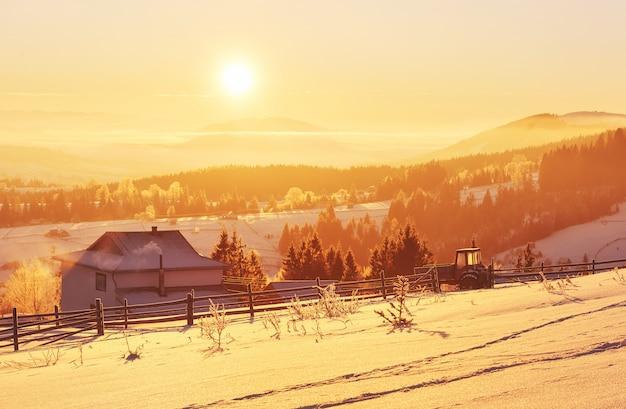 A misteriosa paisagem de inverno é majestosa montanhas no inverno. pôr do sol fantástico. casas de gravação na neve. foto cedida por cartão postal cárpatos
