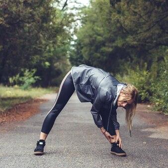 A moça atrativa que faz o esticão ostenta exercícios em um parque da cidade no tempo chuvoso.