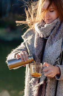 A moça bonita derrama o chá erval de uma garrafa térmica em uma caneca de vidro