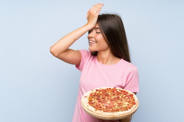 A moça bonita que prende uma pizza sobre a parede azul isolada realizou algo e pretendendo a solução