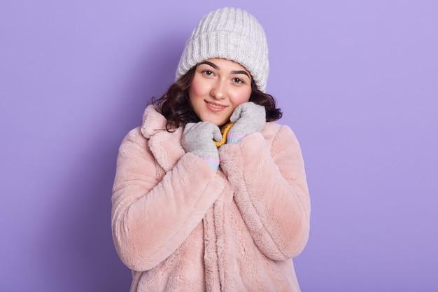 A moça bonita veste o casaco de pele do falso