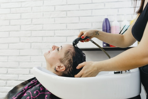 A moça cabeleireira lava delicadamente os cabelos da cliente no salão de beleza.