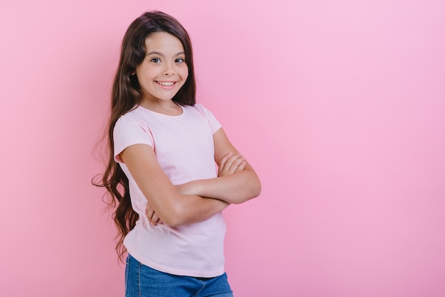 A moça de sorriso com mãos dobradas está vestindo no t-shirt que olha a câmera.