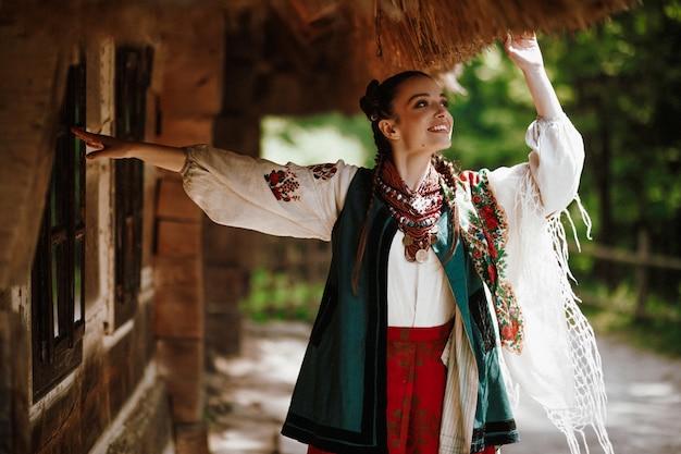 A moça em um vestido ucraniano colorido dança e sorri