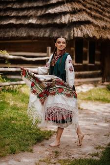 A moça em um vestido ucraniano tradicional colorido dança na rua