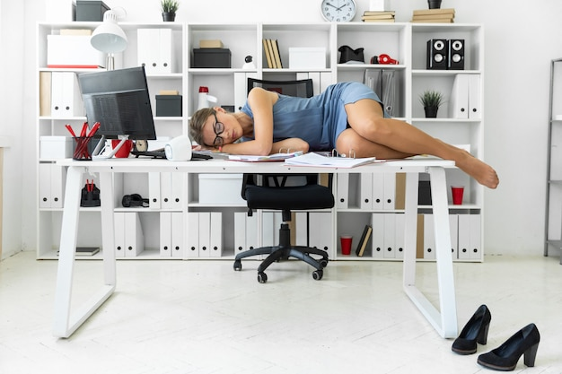 A moça encontra-se com os olhos fechados em originais na mesa no escritório.