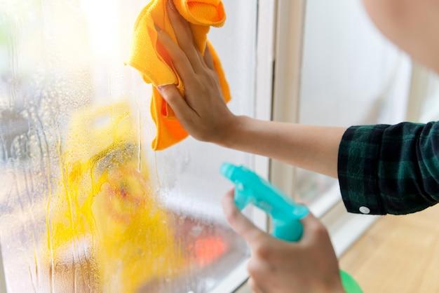 A moça está limpando a janela em casa usando o detergente e o pano.