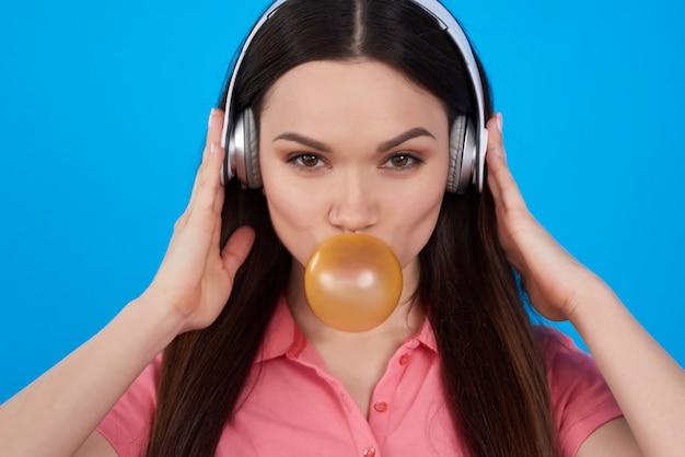 A moça levanta com pastilha elástica nos fones de ouvido.
