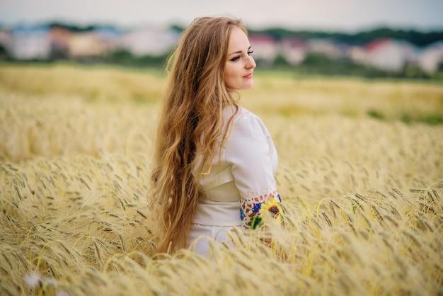 A moça no vestido nacional ucraniano levantou no campo da grinalda.