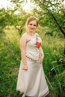 A moça no vestido nacional ucraniano levantou no jardim da mola.