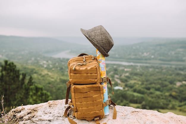 A mochila fica sobre as pedras, em cima dela está um chapéu cinza e um mapa