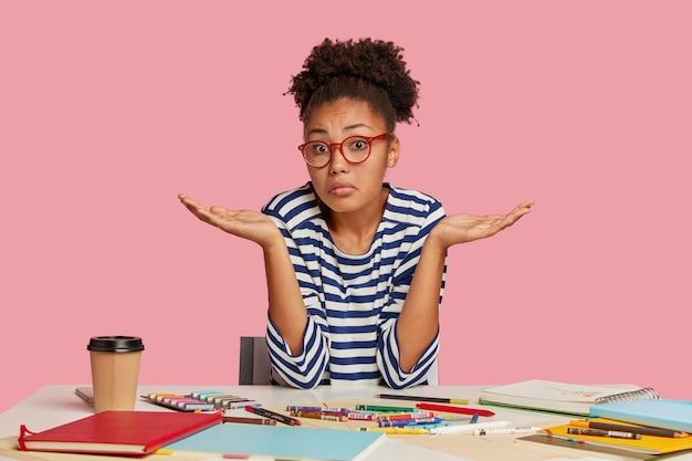 A moda afro-americana perplexa estremece os ombros em perplexidade, vestida com um suéter listrado, cercada por marcadores coloridos