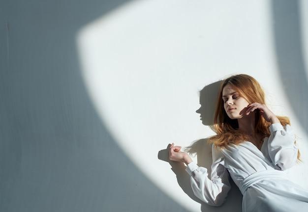A modelo feminina está encostada na parede a sombra cadente de um salão de vestidos de verão branco