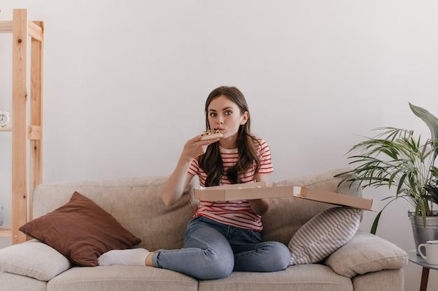 A modelo senta-se em um sofá macio e claro em um ambiente aconchegante e caseiro e come uma pizza deliciosa que acabou de ser entregue