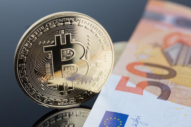 A moeda do bitcoin da moeda criptografada contra a pirâmide de troca de ouro sujeita a notas de euro por dinheiro em conexão com o close up da taxa de câmbio de crescimento ou queda.