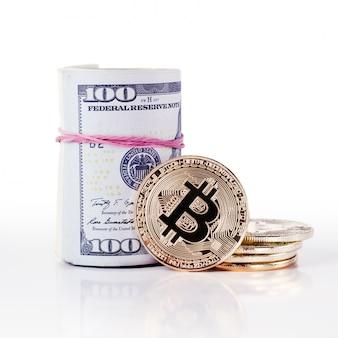 A moeda e a nota de dólar físicas de bitcoin do ouro rolam em um fundo branco.