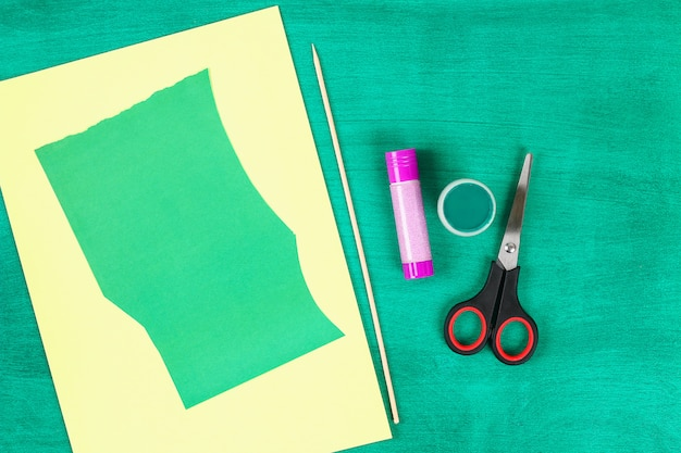 A mola de diy floresce narcisos amarelos do papel amarelo em um fundo verde.