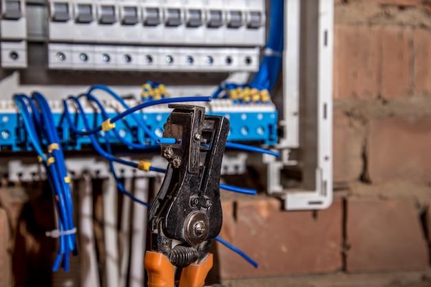 A montagem do painel elétrico, trabalho de eletricista, um robô com fios e disjuntores
