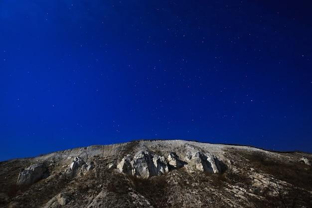 A montanha do cretáceo em um fundo do céu estrelado.