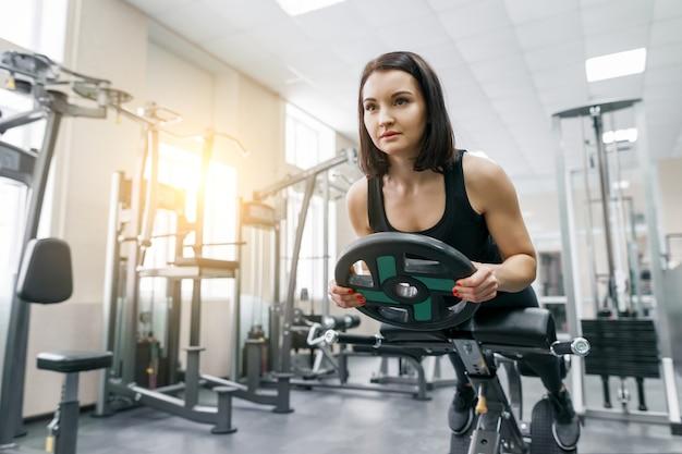 A morena atlética bonita nova da mulher que faz a aptidão exercita no gym.