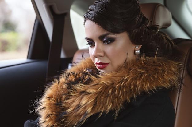 A morena com um casaco de pele no carro