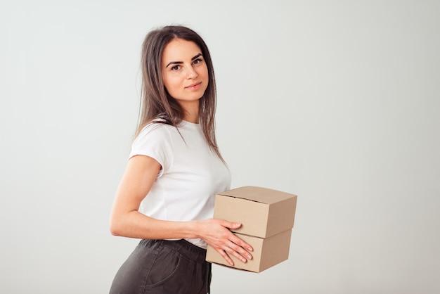 A morena fica de lado com uma caixa nas mãos e sorri docemente. enviando caixas pequenas pelo correio.