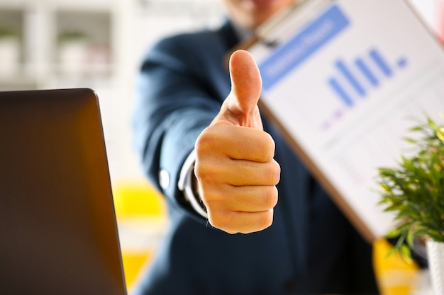 A mostra masculina do braço aprova ou confirma durante a conferência no close up do escritório. produtos de alto nível e qualidade oferecem a expressão correta do símbolo, solução perfeita de mediação, cliente feliz, consultor criativo, participam