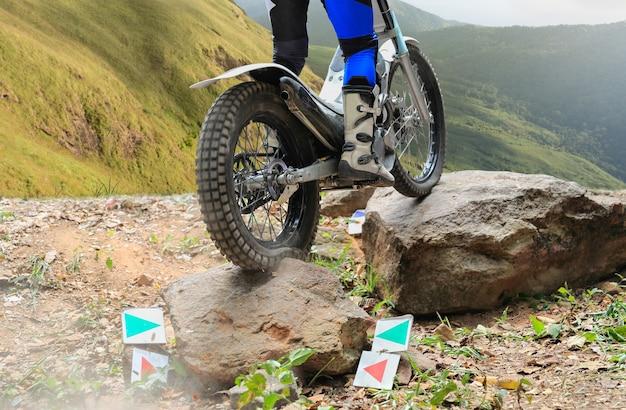 A motocicleta trials está pulando sobre pedras