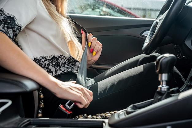 A motorista do sexo feminino está apertando o cinto de segurança. conceito de direção segura
