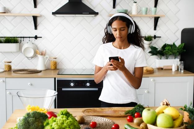 A mulata bonita está segurando o smartphone, em grandes fones de ouvido sem fio, vestindo camiseta branca, perto da mesa com legumes frescos