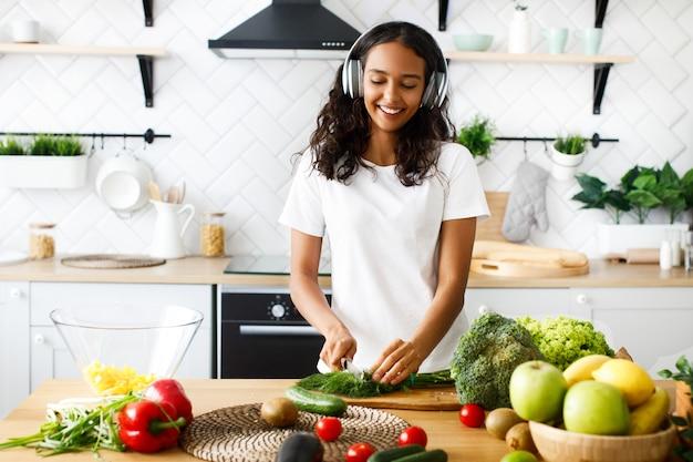 A mulata sorrida em grandes fones de ouvido sem fio está cortando a vegetação na cozinha moderna perto da mesa cheia de legumes e frutas