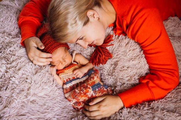 A mulher abraça o bebê recém nascido deitado no cobertor rosa