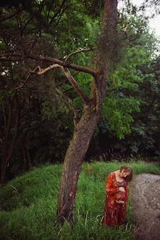 A mulher abraça sua barriga grávida posando na floresta