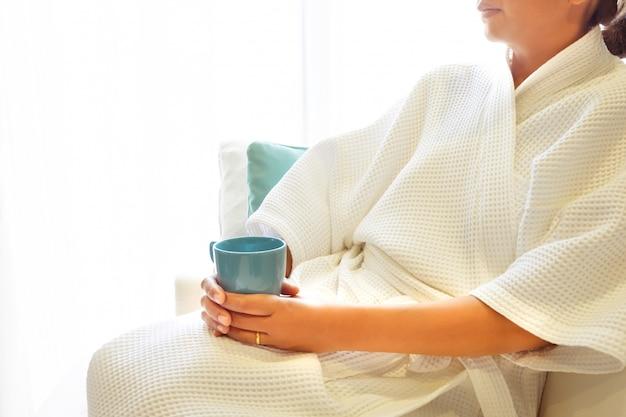 A mulher acordou na mão da manhã que guarda o copo de café quente na sala moderna da cama.